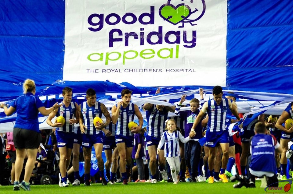 North Melbourne burst through the banner in the first AFL game on Good Friday