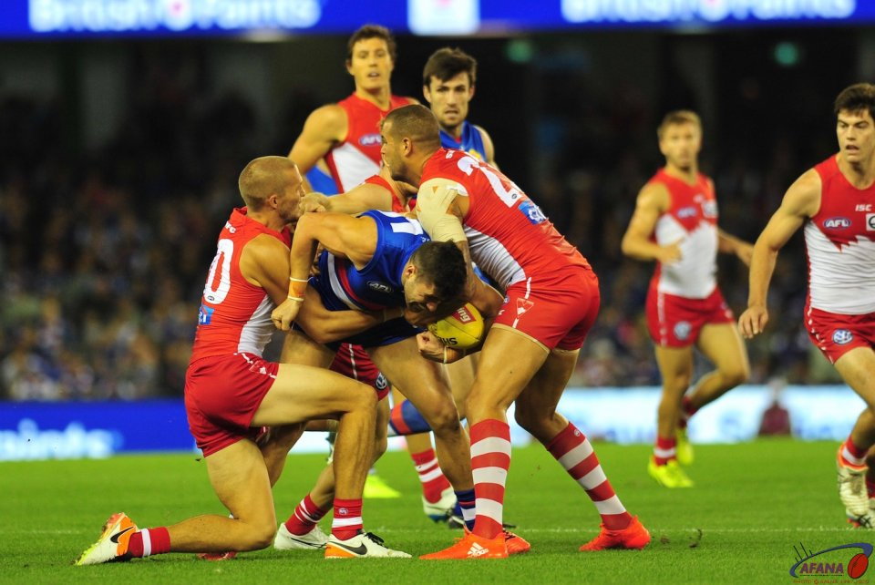 Tom Campbell is tackled by Buddy Franklin (r) and Sam Reid (l)