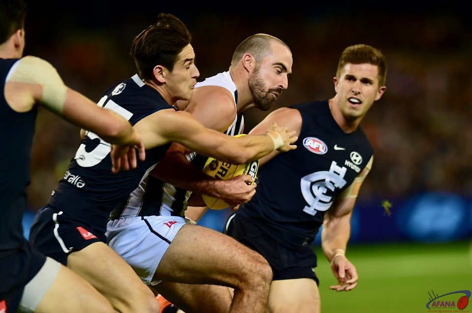 Steele Sidebottom bursts through the Zac Fisher tackle with Blues captain Marc Murphy.