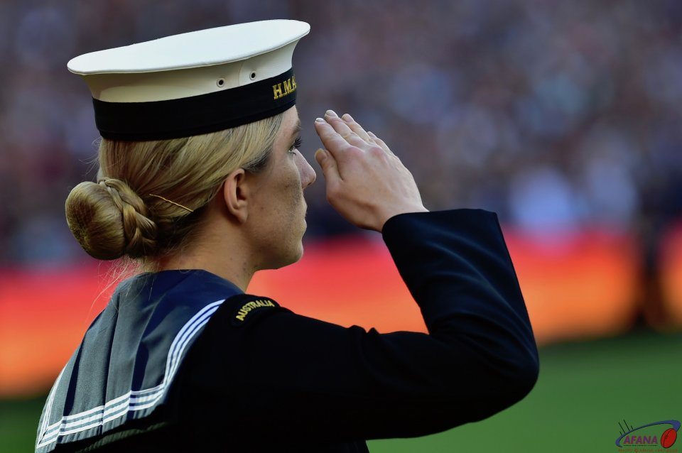 A Sailor salutes during the National Anthem