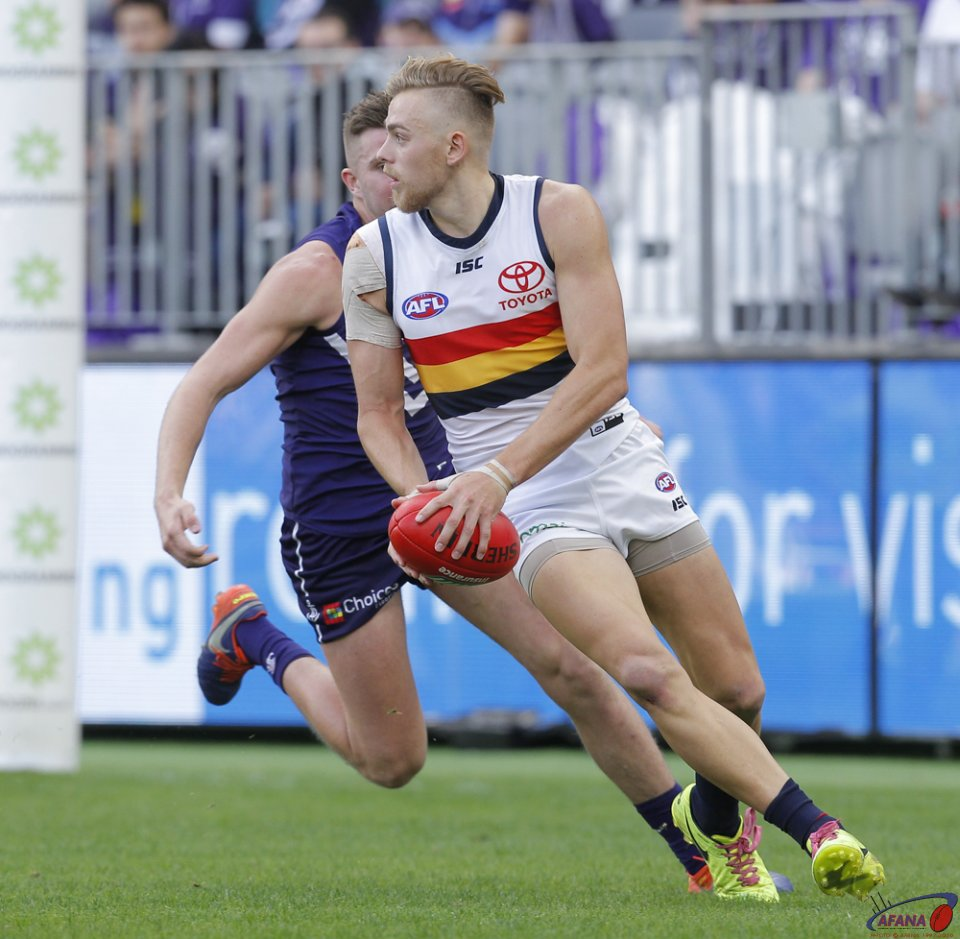 Hugh Greenwood of the Adelaide Crows looks to pass the ball