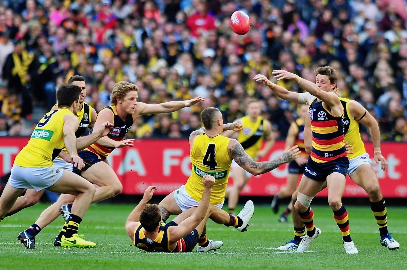 Brad Crouch tackles Dusty as brother Matt and Sloane reach for the sherrin. Photo by Kim Densham for AFANA.