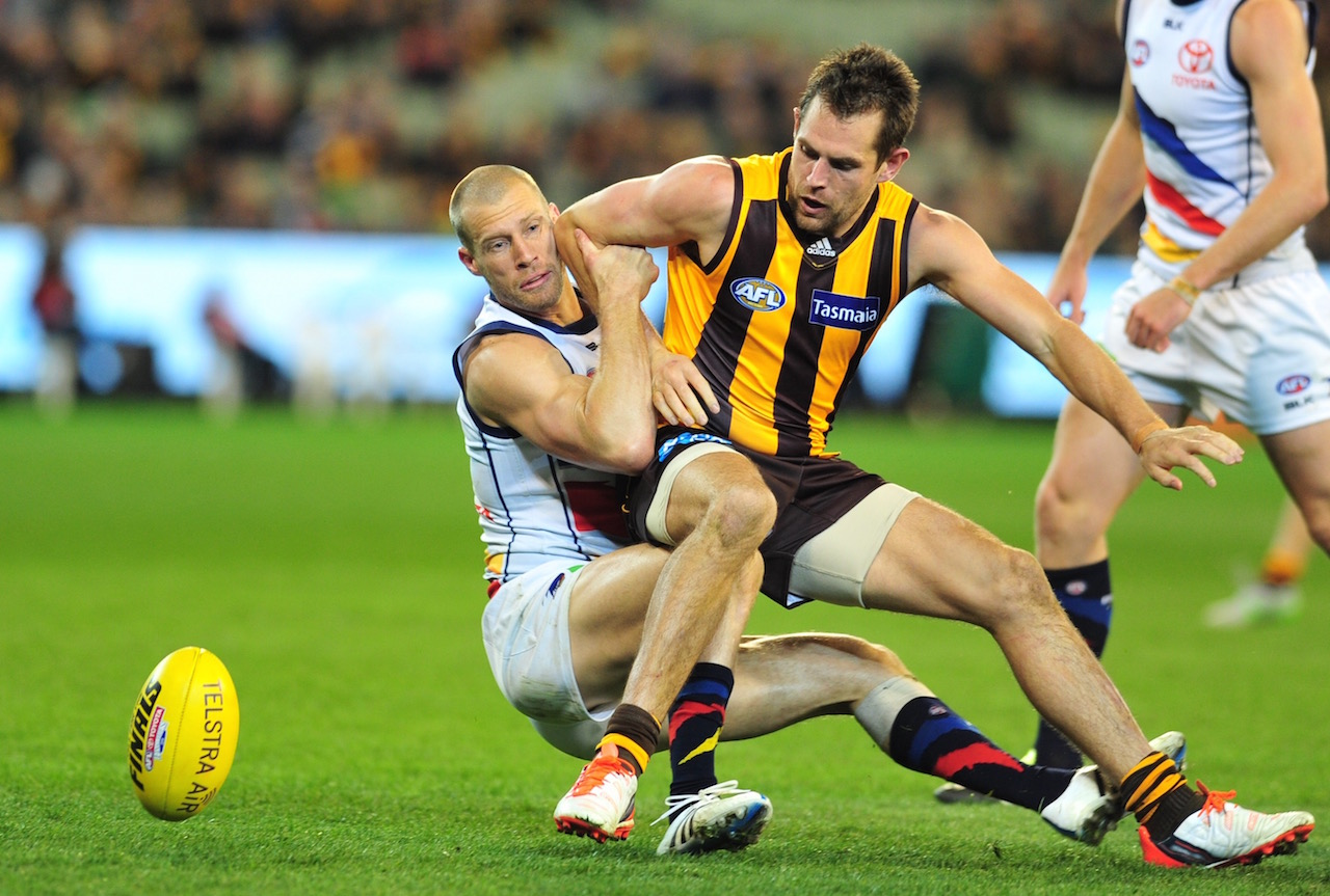 Hawthorn's Luke Hodge Hodge gets trapped by Thompson of the Crows. Photo by Kiim Densham for AFANA.