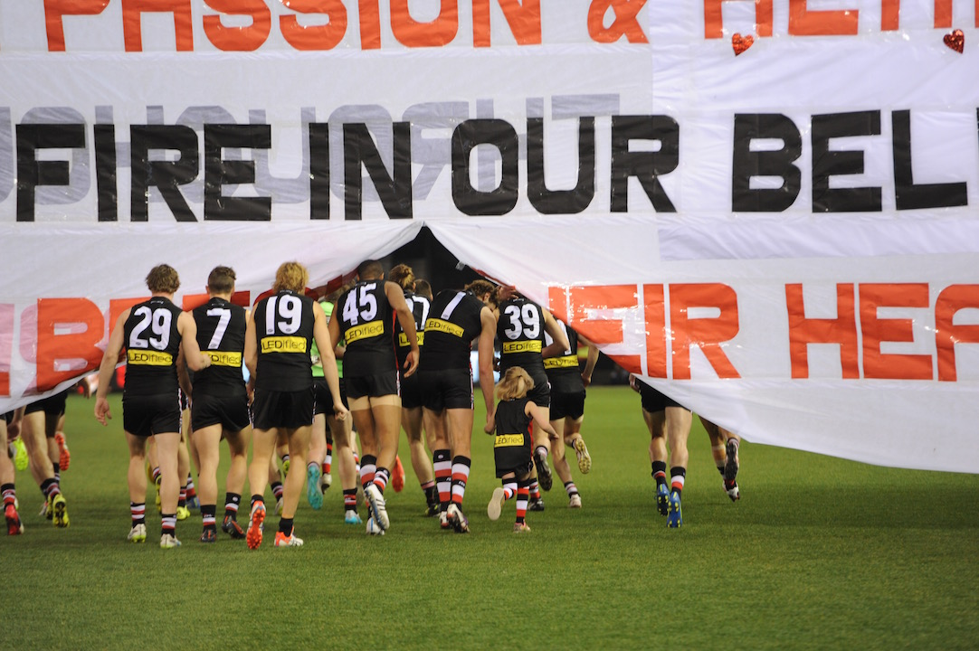 Jason Holmes (45) runs through the banner prior to his debut last weekend in Aussie rules. Photo by Kim Densham for AFANA.