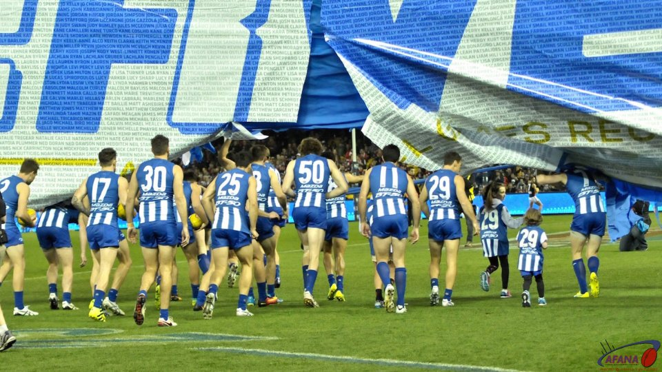 Kangaroos run through the banner honouring Boomer Harvey's 427th game
