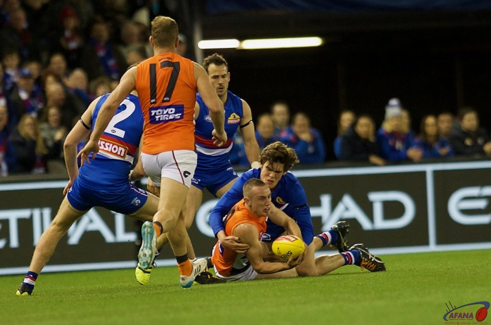 Tom Scully squeezes the handball as Lewis Young tackles