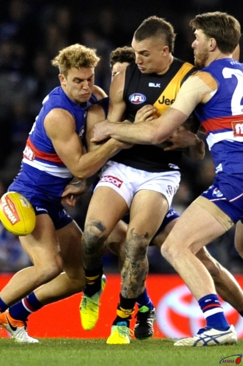 Dustin Martin clears under pressure from Mitch Wallis