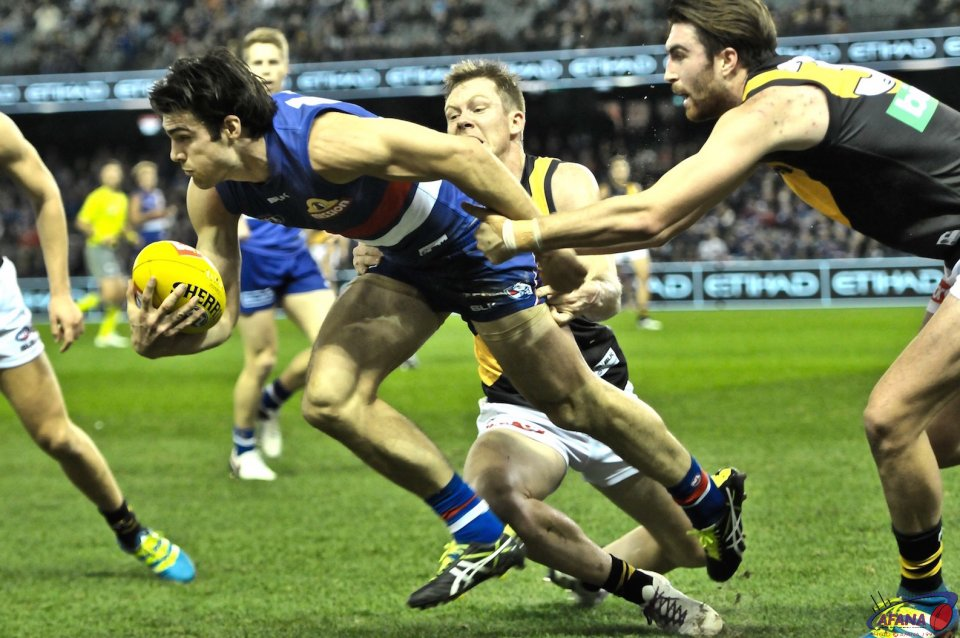 Easton Wood is tackled by Jack Riewoldt and Liam McBean