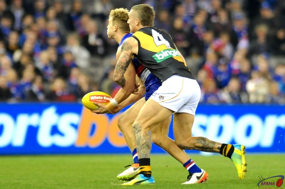 Mitch Wallis is tackled by Dustin Martin
