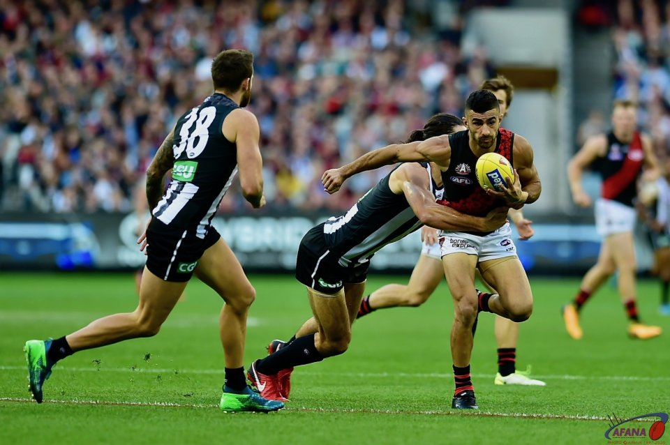 A rampaging Brodie Brundy runs down and tackles Bomber speedster Adam Saad