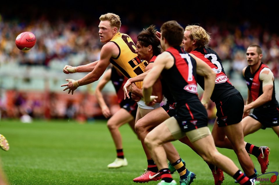 James sicily mobbed by four Bombers handballs forward keeping the pressure on the Bombers defence.